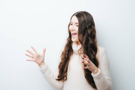 on a white background young girl with long hair rejoices