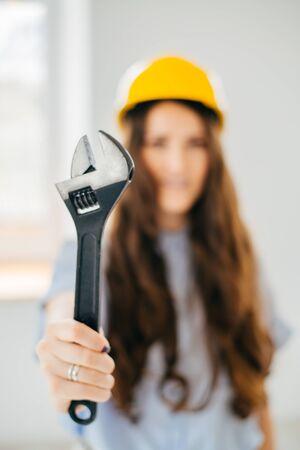 beautiful woman engineer with big screw key near the window Standard-Bild