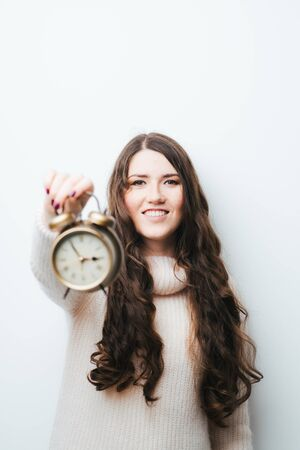 on a white background woman with an alarm clock in hands Stock Photo