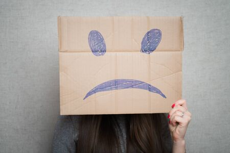 Young woman standing with a cardboard on his head with sad face Reklamní fotografie