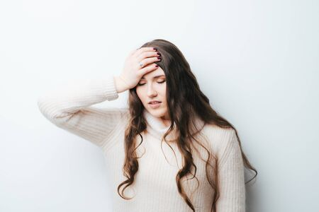 beautiful long-haired girl had a headache and holding his head with hands on a white background