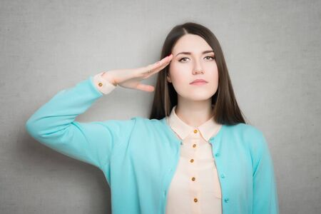 female military salute gesture. isolated on gray background Archivio Fotografico