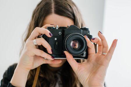 langhaariges brünettes Mädchen auf einer alten Kamera fotografiert