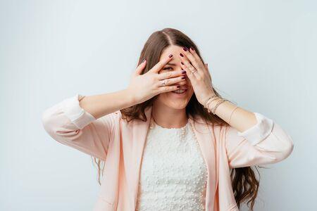 girl looking through fingers