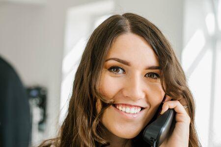 beautiful brunette girl talking on home phone