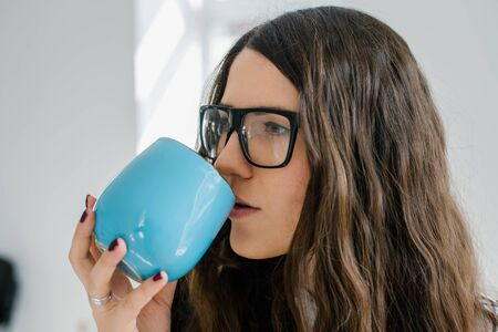 young girl in glasses with blue cup