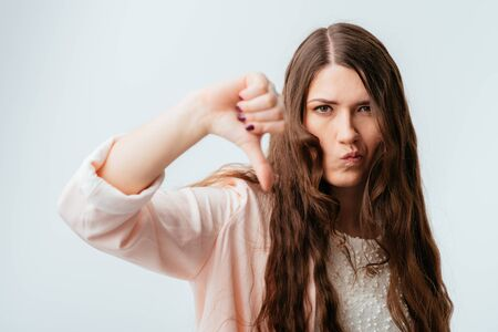 long-haired beautiful brunette girl showing thumb down isolated on white background