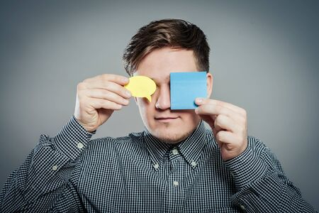 Closeup portrait of young man with a piece of paper covering his eyes on gray background Archivio Fotografico