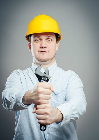 Smiling young mechanic in boiler suit with wrench and arms folded