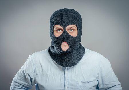 Face of a angry burglar wearing a black ski mask or balaclava