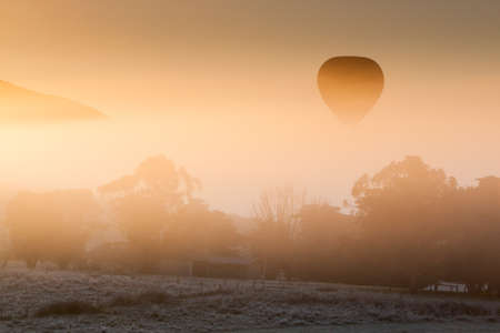 A hot air balloon rises thru the fog just as the sun rises on a cold winter photo