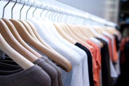 メルボルン、オーストラリアのデザイナー ブランドの洋服店で棚に服を掛ける