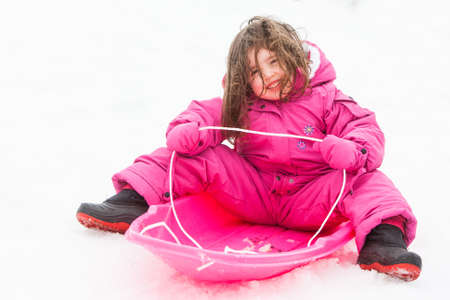 A young girl is ready to toboggan at Lake Mountain in Victoria, Australia photo