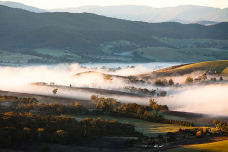 A view across a valley at sunrise in the Yarra Valley in Victoria, Australia