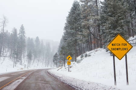 A snowy mountain road with warning signs in Cloudcroft, New Mexico, USA photo