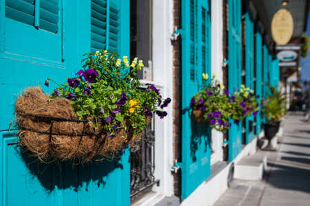 Flowers in baskets hang off shutter doors during Mardi Gras in New Orleans, Louisiana, USA