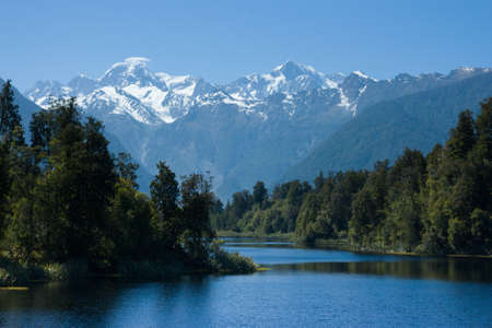 Mt Cook overlooks Lake Matheson on a clear winters morning in New Zealand Stock Photo
