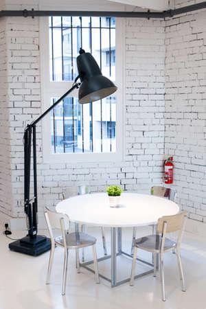 Een moderne tafel, stoel en lamp.