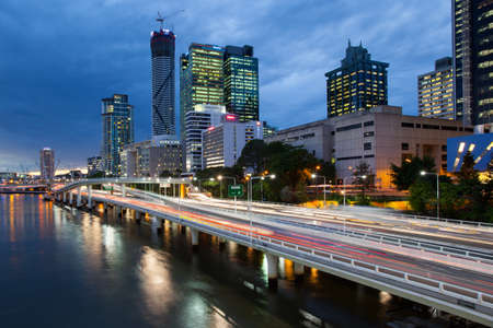 Traffic streams along the Pacific Motorway and Victoria Bridge during rush hour at dusk