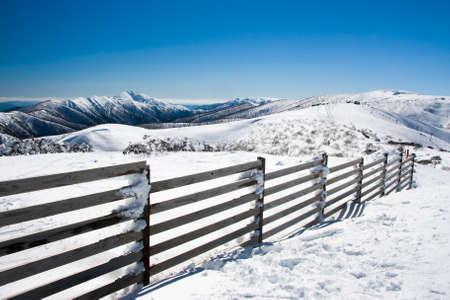 fenceline: Mt Hotham ski resort after fresh snow looking towards Mt Feathertop Stock Photo