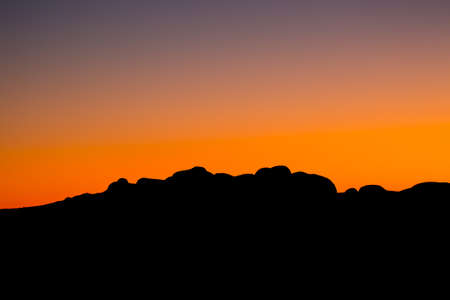 olgas: The silhouette of the boulders of the Olgas at sunset on a clear winters evening in Northern Territory, Australia.