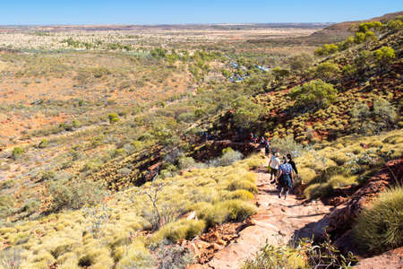 hiking: People hike down a cliff edge at Kings Canyon in Northern Territory, Australia