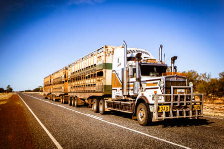 An iconic 3 trailer Australian road train travels along the Plenty Hwy near Gemtree in Northern Territory, Australia