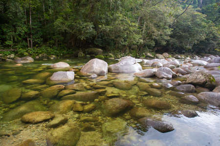 qld: Water of the Mossman River flows over ancient rocks and boulders in Mossman Gorge, Queensland, Australia Stock Photo