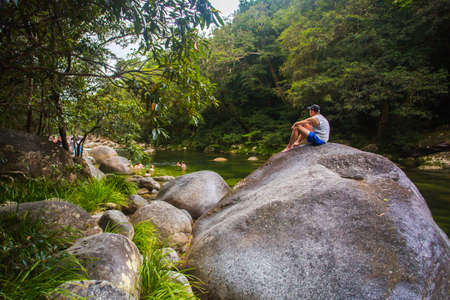 qld: People frolick in the Mossman River as water flows over ancient rocks and boulders in Mossman Gorge, Queensland, Australia Stock Photo
