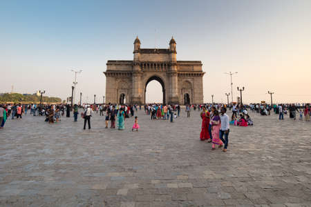 Mumbai, India - 9 November: The Gateway of India with tourists and sellers on a clear autumn evening