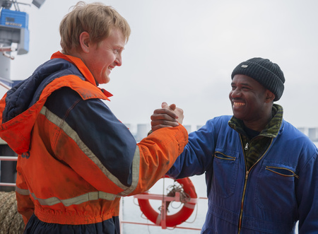 Smiling Europian deck officer wearing orange overall and working gloves friendly shakes a hand of smiling African motorman wearing blue overall on red deck of a ship Stock Photo