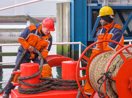 Europian deck officer wearing orange overall and red hardhat working with black ropes together with African sailor wearing orange overall and yellow hardhat on red deck of a ship during mooring operation