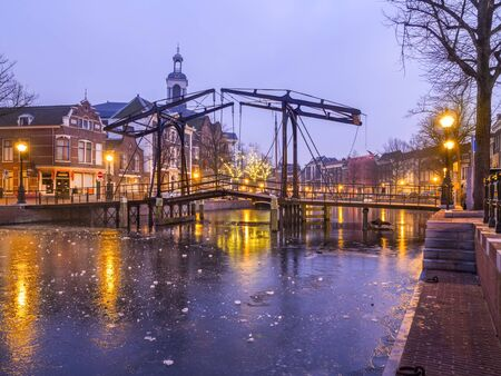 schiedam: Old Dutch city Schiedam evening landscape during freezing weather with reflections in a canal, old bridge and ice on water