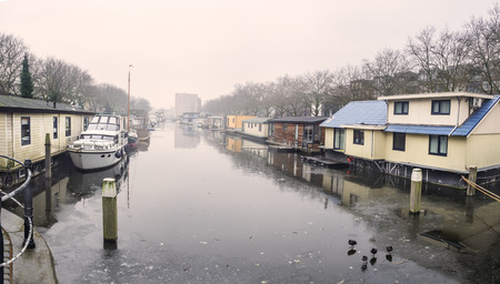 schiedam: Traditional Dutch floating houses on freezing canal in Schiedam, Netherlands Stock Photo