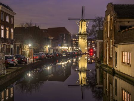 schiedam: Old Dutch city Schiedam landscape during calm weather with reflections in a canal and old windmill Stock Photo