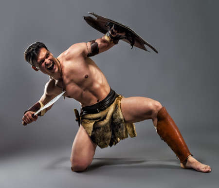 Muscular man in the image of ancient warrior on a gray background