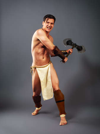 Muscular man in the image of ancient warrior strikes with melee weapons on a neutral grey background
