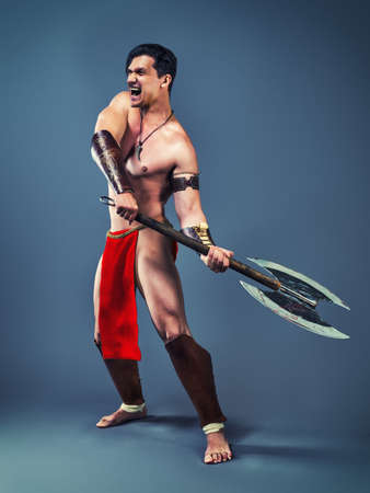 Muscular  man in the image of ancient warrior on a cold blue background. Stock Photo