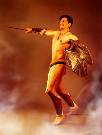 Athletic male in the image of an ancient warrior strikes with a sword on a background of fire, heat and smoke.