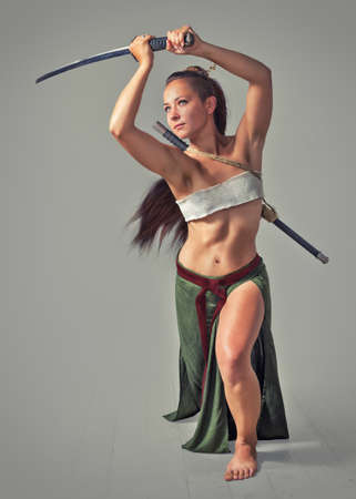 Young flexible girl in the image of the Japanese warrior sword on a light background. The picture is drawn with digital painting. Stock Photo