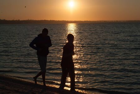 Silhouettes of two young men running on the background of the rising sun over the sea Stock Photo