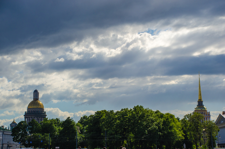 The dome of St. Isaacs Cathedral and the Admiralty in the background of a cloudy sky. St. Petersburg Russia