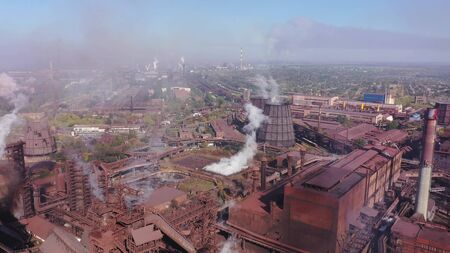 Ecological catastrophy. Aerial view of blast furnaces and cooling towers. Smog in the city. Фото со стока