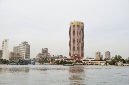 Cairo, Egypt - January 14, 2020 : Buildings on the banks of the Nile in Cairo. View from a floating boat. Overcast sky Redactioneel