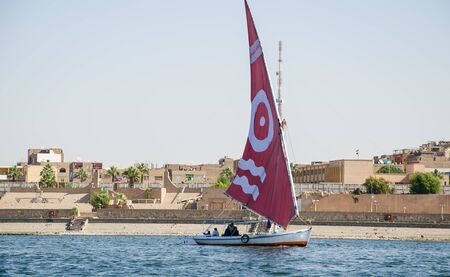 Luxor, Egypt - January 16, 2020 : Felucca sailboat on the Nile river near Luxor, Egypt. A felucca is a traditional wooden sailing boat