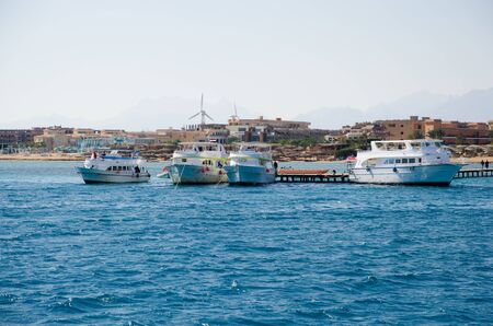 Yacht and motor boat at the pier. The shore of the Red Sea. View from the sea 免版税图像
