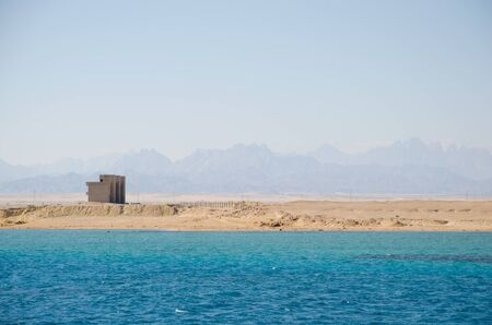 Beautiful coastline of the Red Sea in Egypt. View from a floating ship. In the background are silhouettes of mountains.