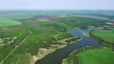 Aerial view of a picturesque reservoir. Near the pond, you can see a forest and agricultural fields. Spring time Archivio Fotografico