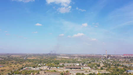Aerial view. A panoramic view of an industrial plant. Black smoke against the blue sky. Environmental pollution.