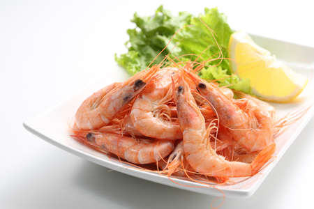 dish of fresh boiled prawns with lettuce, isolated on grey photo